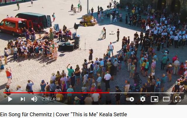 """Auf dem sonnigen Chemnitzer Marktplatz stehen Menschen in Abstand um eine Bühne. Auf der Bühne singt eine junge Frau """"This is me"""" begleitet von einer Band. Links und rechts daneben steht der Gebärdenchor. Vor der Bühne singt ein kleiner Chor buntgekleideter Menschen."""